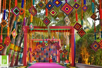 Colourful mehendi entrance decor with hanging patterns