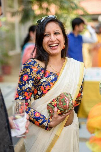 Blue embroidered blouse with white and gold saree