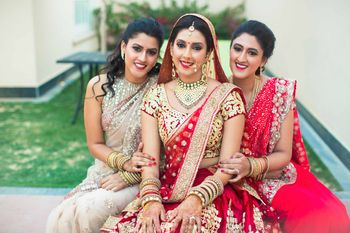 Bride in red and gold lehenga with bridesmaids