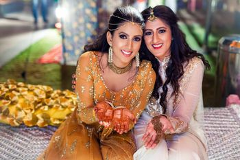 Bride in marigold anarkali with sister on mehendi
