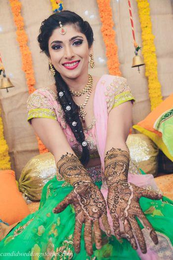 Bride in floral lehenga showing off mehendi hands