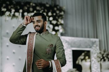 Photo of Groom wearing a sage green bandhgala with white stole