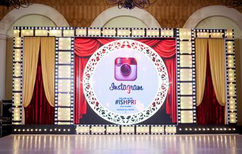 Theatre theme sangeet with instagram hashtag on stage