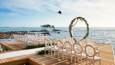 Photo of simple mandap for beachside wedding with chairs