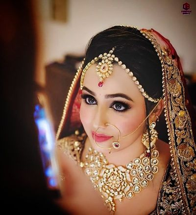 Photo of A bride with peach and gold jewelry poses for the camera.