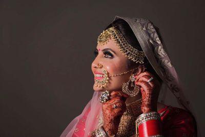 Photo of Bride adjusting jewellery for bridal portrait