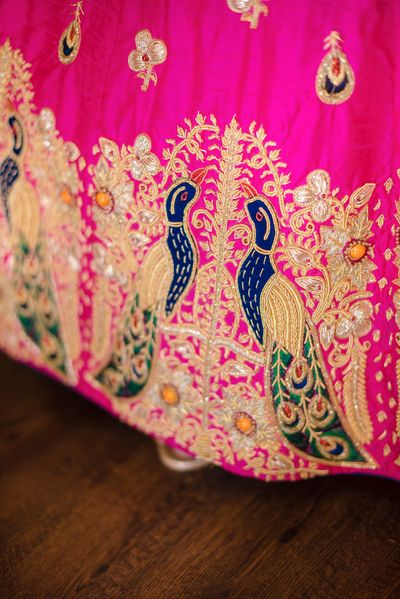 Photo of Bright pink lehenga with peacock embroidery