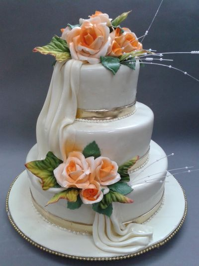 Photo of White and Gold 3 Tier Wedding Cake with orange Flowers