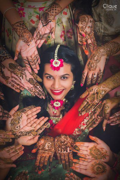Photo of Bride and bridesmaids showing off mehendi bridal portrait