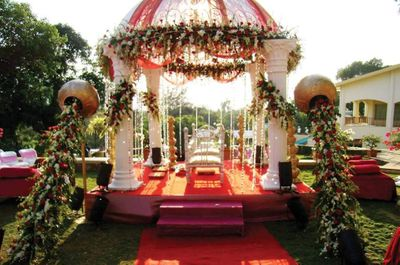 Photo of Gold pots with spilling flowers in front of white mandap
