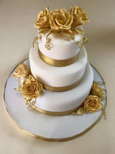 Photo of 3 tier white wedding cake with gold flowers