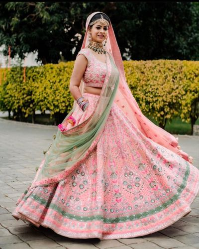 Photo of Bride twirling around in a baby pink lehenga.