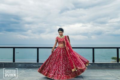 Photo of Red and gold bridal lehenga with sea facing view
