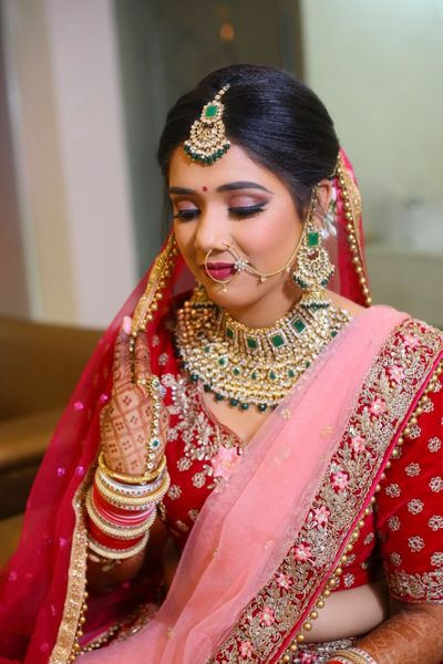 Photo of A bride in red and pink outfit with exquisite bridal jewelry