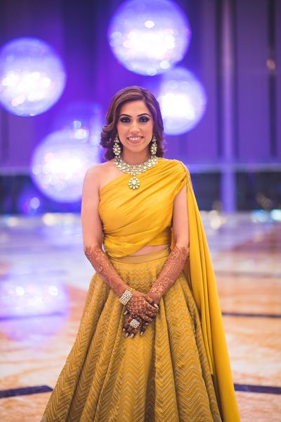 Photo of Yellow lehenga for sangeet with one shoulder blouse