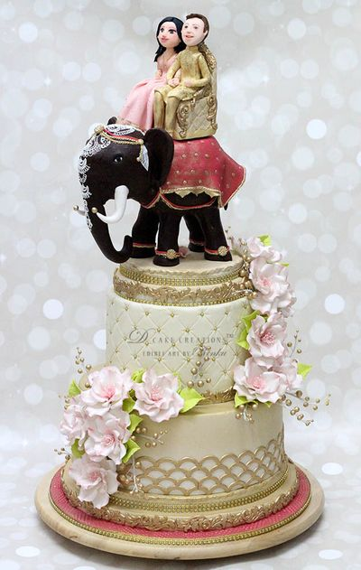 Photo of Gold destination wedding cake topper with couple on elephant