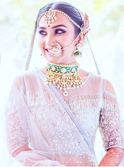 Photo of Contrasting jewellery with white lehenga and green choker