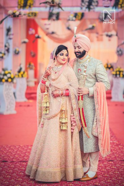 Photo of Coordinated Sikh bride and groom in peach