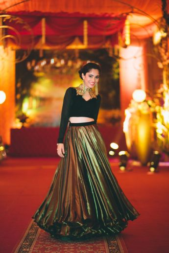 Photo of metallic gold lehenga with black velvet crop top high neck and edgy gold detailing around neckline