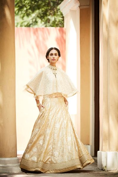 Photo of Off white and gold cape lehenga with benarasi skirt