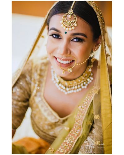 Photo of A bride in golden lehenga and minimal jewelry