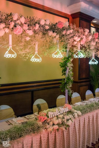 Photo of peach pink and green table setting indoor banquet with hanging trellis of flowers
