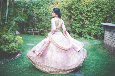 Photo of Bride twirling in light pink engagement lehenga