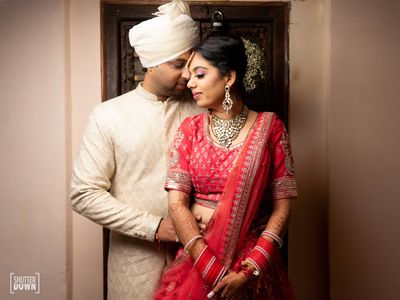 Photo of A bride and groom in red and beige attires for their wedding