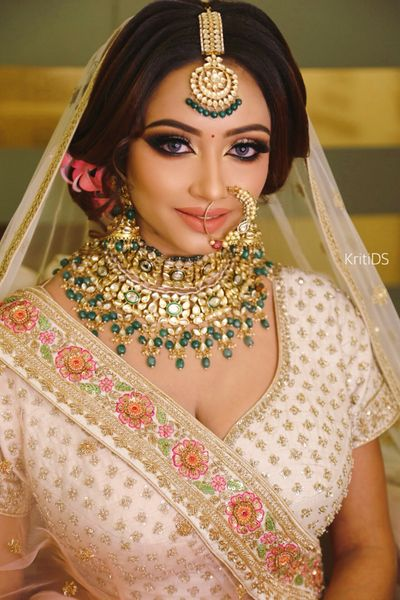 Photo of A bride in peach outfit and unique jewellery