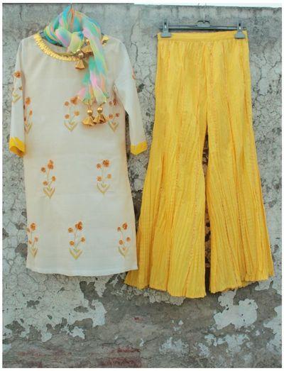 Photo of wide legged pallazo pants in yellow with white kurta and gota work. tie dye dupatta