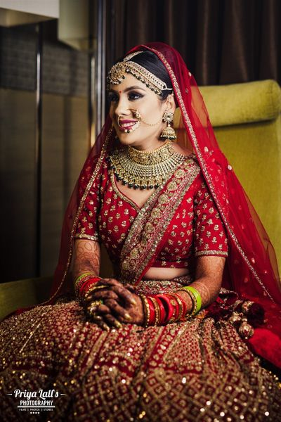 Photo of A bride in a red lehenga and gold jewelry for her wedding