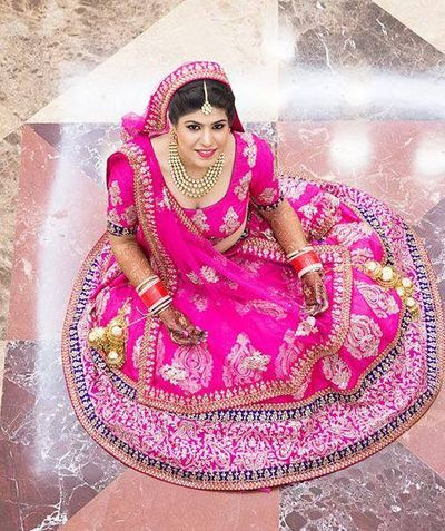 Photo of bridal lehenga in hot pink fuschia and blue