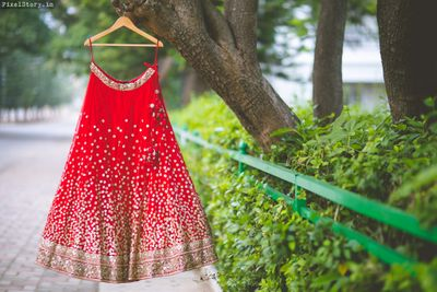 Photo of Red Bridal Lehenga with Gold Sequins on a Hanger
