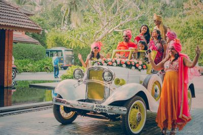 Photo of Bride entering in vintage car with family