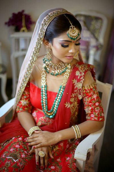 Photo of Bride in red and gold bridal outfit with green jewellery and cold shoulder