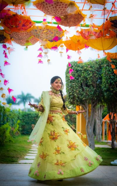 Photo of A bride in a green lehenga twirling on her mehndi