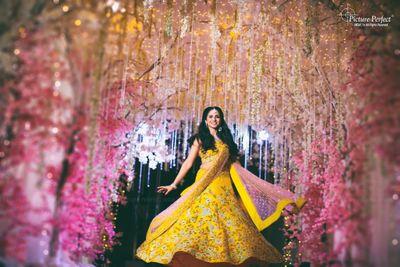 Photo of Mehendi lehenga bride twirling