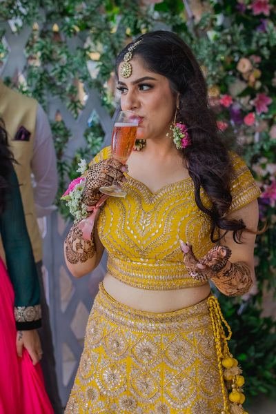 Photo of bride drinking juice on mehendi or haldi photo