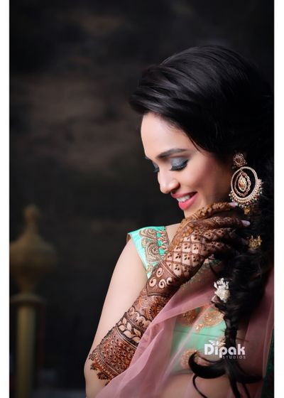 Photo of Bride with smokey eyes showing off mehendi