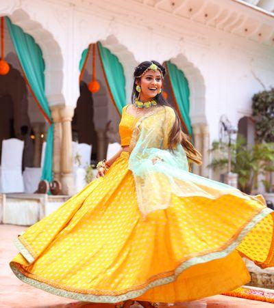 Photo of Bride twirling in a bright yellow mango coloured lehenga on her mehendi