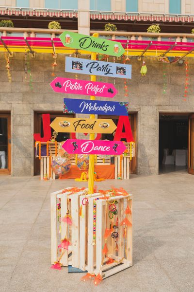 Photo of Cute mehendi decor idea with direction boards