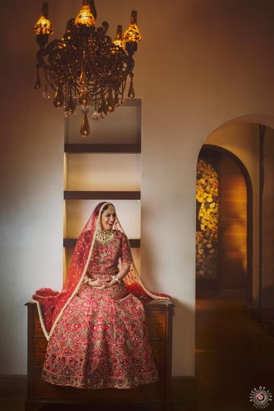 Photo of happy bride in red floral embroidery lehenga