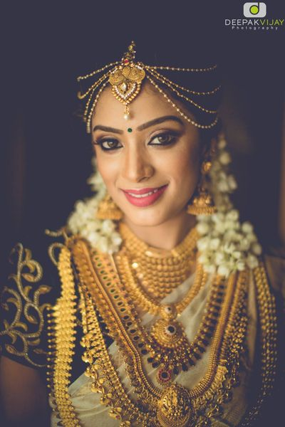 Photo of South Indian bride with layered necklaces in gold