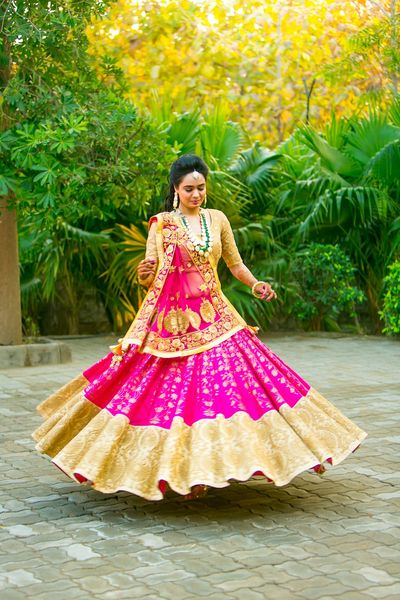 Photo of Bride twirling in gold and pink lehenga with broad border