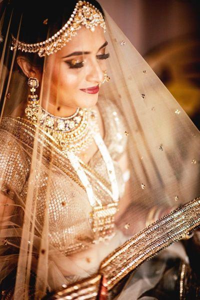 Photo of Beige bridal lehenga with dupatta as veil