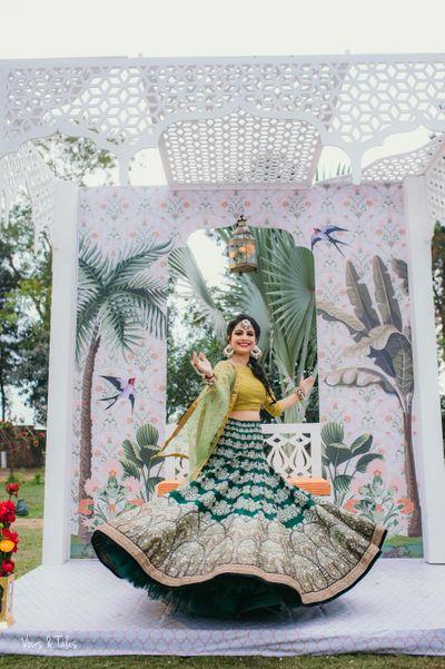 Photo of Bride twirling in dark and light green mehendi lehenga