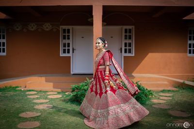 Photo of A bride twirling in a red lehenga