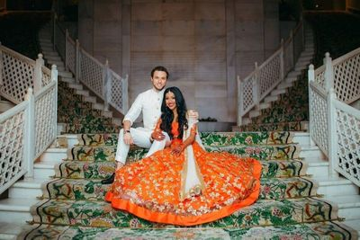 Photo of A bride in orange lehenga with her groom