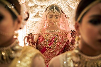 Photo of bridal entry with her holding her dupatta as a veil