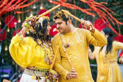 Photo of couple playing dandiya on haldi or mehendi